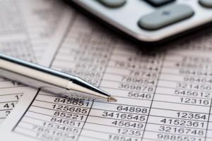 Ein Taschenrechner liegt auf den Zahlen einer Bilanz und Statistik. Symbolphoto für Umsatz, Gewinn und Kosten. kwp Dachau Wirtschaftspruefer Steuerberater Testamentsvollstrecker